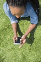 Black woman using cell phone in grass