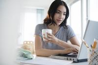 Hispanic woman using laptop at desk