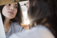 Hispanic woman applying mascara in mirror