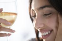 Hispanic woman holding glass of wine