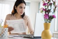 Hispanic woman paying bills on laptop