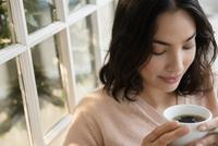 Hispanic woman drinking cup of coffee