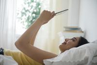 Hispanic woman using digital tablet in bed