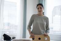 Hispanic businesswoman smiling in office