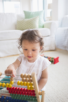 Mixed race baby girl playing with abacus