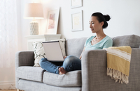 Japanese woman using laptop on sofa