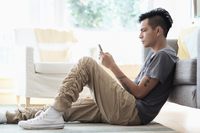 Asian man using cell phone in living room