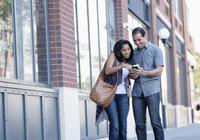 Hispanic couple using cell phone outdoors