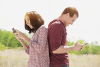 Hispanic couple using cell phones outdoors