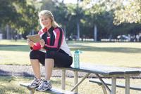 Caucasian woman using digital tablet in park