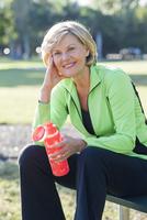 Caucasian woman drinking water bottle in park