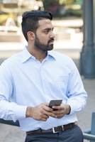 Indian businessman using cell phone in city
