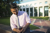 Indian businessman using cell phone outside office building