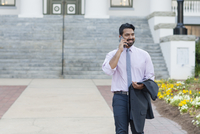 Indian businessman talking on cell phone on sidewalk