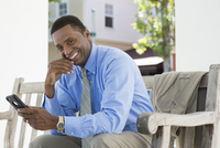 Black businessman using cell phone on bench