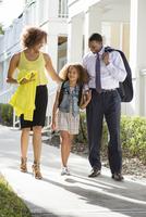 Parents walking daughter to school
