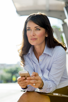 Caucasian businesswoman using cell phone at bus stop