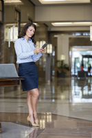 Caucasian businesswoman using cell phone in lobby