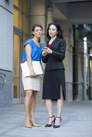 Caucasian businesswomen using cell phone outdoors