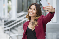 Hispanic businesswoman taking selfie outdoors