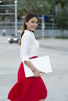 Hispanic businesswoman carrying laptop outdoors