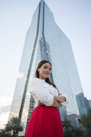 Hispanic businesswoman standing near highrise