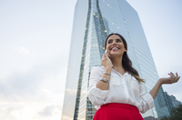 Hispanic businesswoman talking on cell phone outdoors
