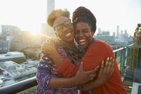 Women hugging on city rooftop