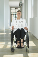 Caucasian doctor in wheelchair holding empowering sign