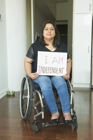 Indian woman in wheelchair holding empowering sign