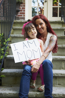 Caucasian mother and daughter holding empowering sign