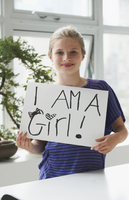 Caucasian girl holding empowering sign