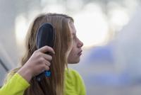 Caucasian girl brushing her hair outdoors