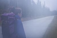 Caucasian hiker walking on remote road