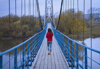 Caucasian girl walking on bridge
