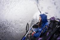 Caucasian hiker riding ski lift