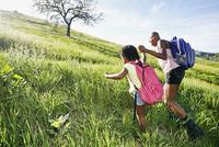 Black mother and daughter walking on rural hillside