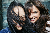 Women laughing with hair blowing in wind