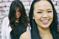 Women smiling at brick wall