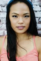 Serious Asian woman at brick wall