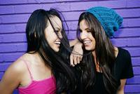 Women laughing near purple brick wall