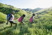Black mother and daughters walking on rural hillside