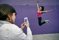 Woman photographing friend jumping for joy