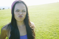Asian woman making a face outdoors