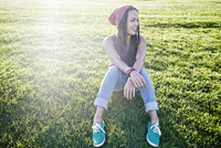 Asian woman sitting in grass