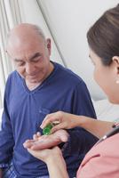 Hispanic nurse giving patient medication