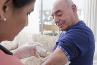 Hispanic nurse giving patient injection
