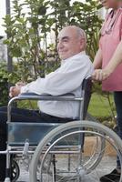 Hispanic nurse pushing patient in wheelchair