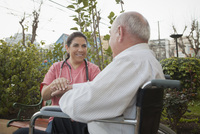 Hispanic nurse comforting patient in wheelchair