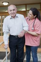 Hispanic nurse helping patient walk with crutch